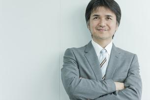 腕を組んで微笑む日本人ビジネスマンの写真素材 [FYI01620107]