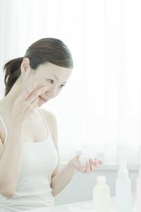 鏡の前でクリームをぬる女性のスキンケアイメージの写真素材 [FYI01620117]