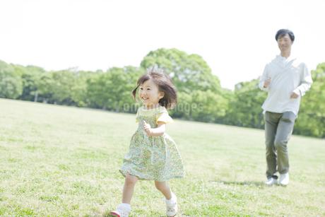 公園を走る笑顔の女の子の写真素材 [FYI01620120]
