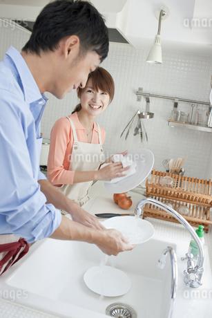 キッチンに立つ若い夫婦の写真素材 [FYI01620125]