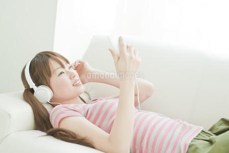 ソファーで音楽を聴く若い日本人女性の写真素材 [FYI01620158]
