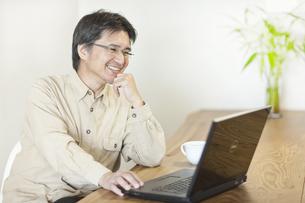自宅でパソコンをする日本人男性の写真素材 [FYI01620178]