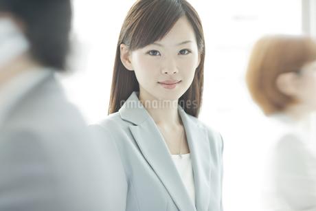 スーツ姿でオフィスに立つビジネスウーマンの写真素材 [FYI01620207]