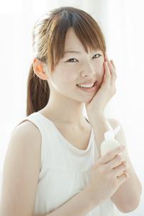 ローションを持つ若い女性の写真素材 [FYI01620211]
