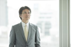 窓際に立ち考えるビジネスマンの写真素材 [FYI01620220]