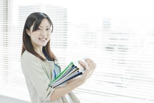 書類を抱え持つ女性社員の写真素材 [FYI01620221]