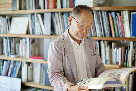 本棚の前で書籍を広げるシニア男性の写真素材 [FYI01620226]
