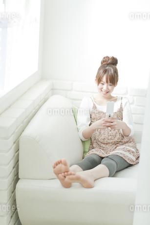 ソファーでメールをする若い日本人女性の写真素材 [FYI01620237]