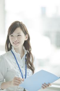 ファイルを持ち振り向く笑顔のビジネスウーマンの写真素材 [FYI01620240]