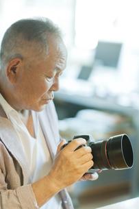 一眼レフカメラを持つシニア男性の写真素材 [FYI01620241]