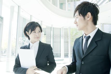 打ち合わせする若いビジネスマンとビジネスウーマンの写真素材 [FYI01620246]