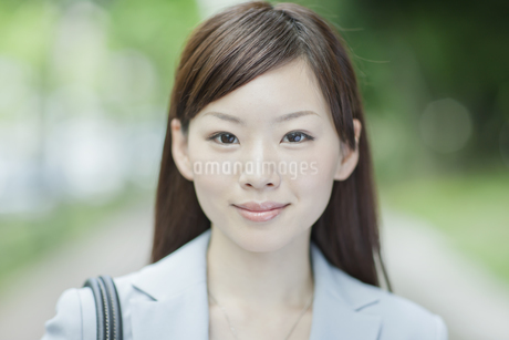 並木道を歩く笑顔のビジネスウーマンの写真素材 [FYI01620273]