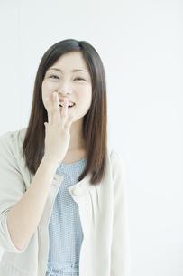 口に手をあてて笑う若い女性の写真素材 [FYI01620281]