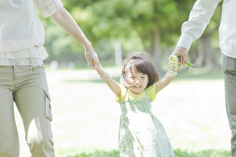 両親と手を繋ぎ喜ぶ女の子の写真素材 [FYI01620291]