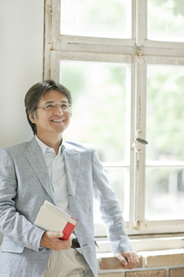 窓際に立ち本を持つミドル男性の写真素材 [FYI01620292]
