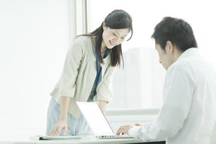 男性社員のパソコンをのぞく女性社員の写真素材 [FYI01620304]