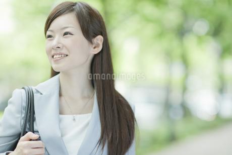 並木道を歩く笑顔のビジネスウーマンの写真素材 [FYI01620312]
