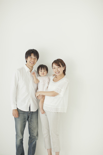 赤ちゃんを抱っこする笑顔の父親と母親の写真素材 [FYI01620318]