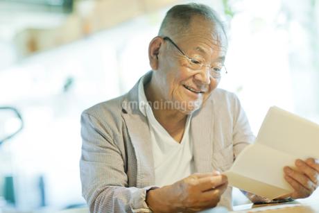 手紙を読むシニア男性の写真素材 [FYI01620346]