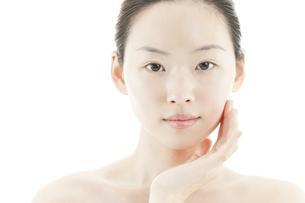 片手を頬に添える若い女性のスキンケアイメージの写真素材 [FYI01620373]