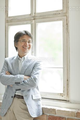 窓際に立つミドル男性の写真素材 [FYI01620379]