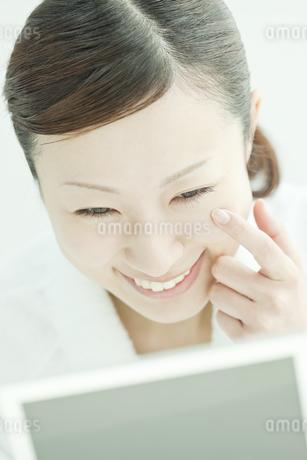 鏡の前で喜ぶ女性のスキンケアイメージの写真素材 [FYI01620389]