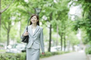 並木道を笑顔で歩くビジネスウーマンの写真素材 [FYI01620392]