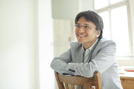 椅子の背もたれにもたれるミドル男性の写真素材 [FYI01620393]
