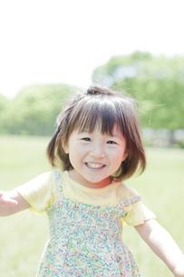 公園を走る笑顔の女の子の写真素材 [FYI01620395]