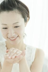 化粧水を手に取り暖める女性 美容とスキンケアイメージの写真素材 [FYI01620406]