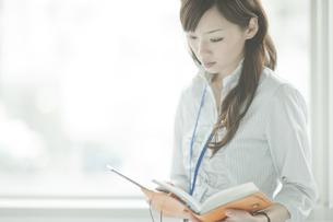 手帳を見ながら携帯電話をかけるビジネスウーマンの写真素材 [FYI01620416]