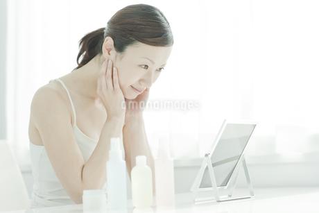 鏡を覗き込む女性のスキンケアイメージの写真素材 [FYI01620420]