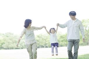 公園で手を繋いで歩く3人家族の写真素材 [FYI01620433]