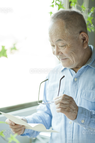 手紙を読むシニア男性の写真素材 [FYI01620435]