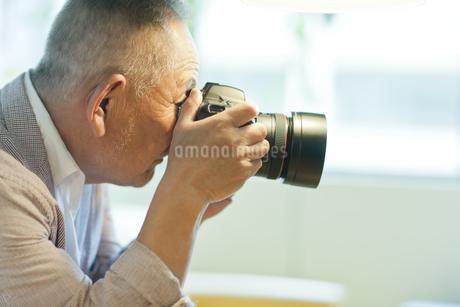 一眼レフカメラを持つシニア男性の写真素材 [FYI01620445]