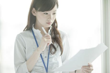 書類を持ち考えるビジネスウーマンの写真素材 [FYI01620449]