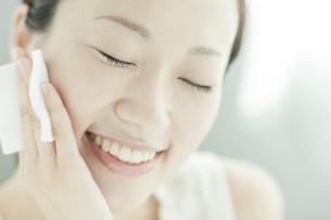 コットンを顔に置く女性 美容とスキンケアイメージの写真素材 [FYI01620457]