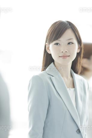 スーツ姿でオフィスに立つ笑顔のビジネスウーマンの写真素材 [FYI01620466]