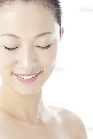 目を閉じて微笑む女性のスキンケアと美容イメージの写真素材 [FYI01620497]