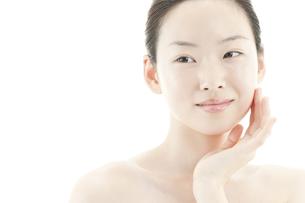 片手を頬に添える若い女性のスキンケアイメージの写真素材 [FYI01620502]