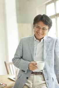 コーヒーカップを持つミドル男性の写真素材 [FYI01620505]