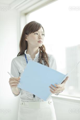 ファイルを持ち窓の外を見るビジネスウーマンの写真素材 [FYI01620507]