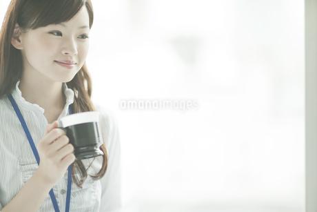 窓のそばに立ちコーヒーカップを持つビジネスウーマンの写真素材 [FYI01620508]