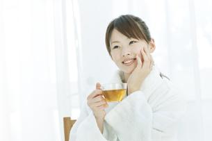 エステサロンで施術後ハーブティーを飲む若い女性の写真素材 [FYI01620511]