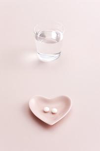 ハートの小皿に入れられた薬の写真素材 [FYI01620534]