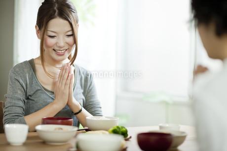 食事のテーブルにつき手を合わせる若い夫婦の写真素材 [FYI01620537]