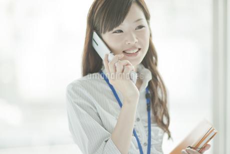 手帳を持ち携帯電話をかけるビジネスウーマンの写真素材 [FYI01620544]