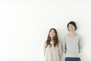 寄り添い見上げる笑顔の若い夫婦の写真素材 [FYI01620558]