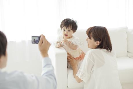 赤ちゃんと母親を撮影する父親の写真素材 [FYI01620564]