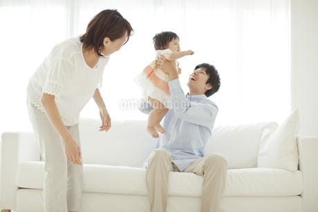 ソファーに座り赤ちゃんを抱き上げる父親の写真素材 [FYI01620565]